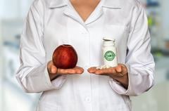 Young doctor holding fresh apple and bottle of pills with vitamins and compare - stock photo