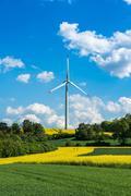 Wind turbine in a rapeseed field, ECO energy power - stock photo