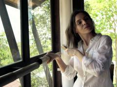 Stock Video Footage of Beautiful woman combing her hair standing by window NTSC