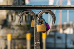 Love padlocks or love locks on a railing in the harbor of Lindau Stock Photos