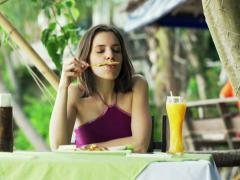 Young woman eating satay chicken sitting in exotic cafe NTSC Stock Footage