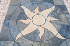Stone floor tiles with sun motif - stock photo