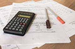 Calculator and two pens on bank statement on the table - stock photo