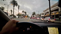 POV driver hand steering wheel approaching stop light crosswalk intersection LA Stock Footage