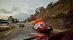 Two kids pulled over ticket police car lights flashing PCH road highway Santa M Stock Footage