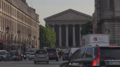 La Madeleine church in Paris, french cityscape with crowded avenue, cars move Stock Footage