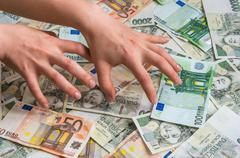 Stingy hands takes czech and euro money Stock Photos