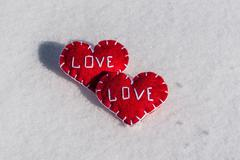 Beautiful hearts on a snow backgroud - always together - stock photo