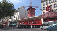Parisian car traffic in summer in front of cabaret moulin rouge, world famous Stock Footage