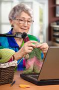 Stock Photo of Learning to knit under webcam