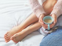 Woman relaxing at cozy home atmosphere on the bed. Young woman with beautiful Stock Photos
