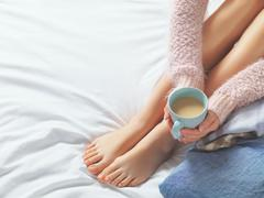 Woman relaxing at cozy home atmosphere on the bed. Young woman with beautiful - stock photo