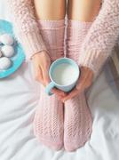 Woman relaxing at cozy home atmosphere on the bed. Young woman with cup of mi Stock Photos