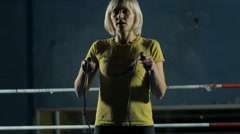 Close-up of blonde jumping on a rope in a dark room Stock Footage