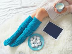 Woman using tablet at cozy home atmosphere on the bed. Young woman with cup o Stock Photos