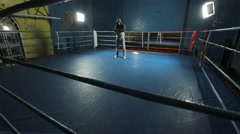 Man in sportswear standing on a dark boxing ring and winds the bandage on his Arkistovideo