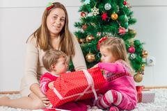 Christmas Happy Family mother and her two little daughters sitting on the flo - stock photo
