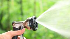 Man Watering Lawn By Spraying Hose. background, bokeh, focus. Stock Footage