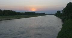 Orange, Yellow Sunset, River, Green Overgrown Banks Stock Footage
