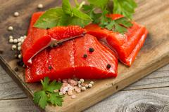 Top view shot of fresh bright red Copper River salmon fillets on cutting boar - stock photo