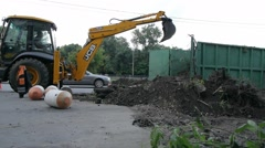 Heavy excavator unloading sand during road construction works Stock Footage