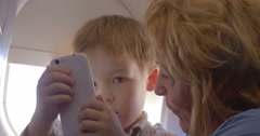Grandmother talking to grandson in the plane Stock Footage