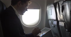 Young businessman working with pad in plane - stock footage