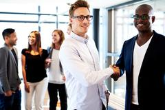 Black man and white man shaking hands - stock photo