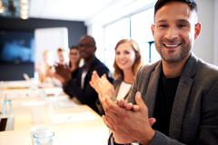 Group of executives facing camera and clapping Stock Photos