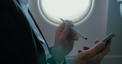 Businessman using smart phone during the flight - stock footage