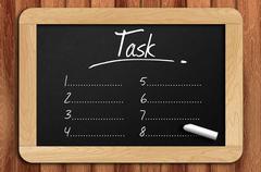 Chalkboard on the wooden table written task list - stock photo