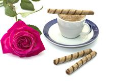 Cup of coffee on a saucer and a bright rose Stock Photos