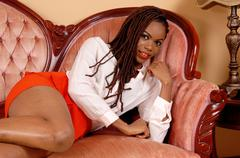Pretty African woman lying on couch. - stock photo