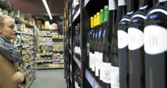 Woman in the store choosing bottle of wine Stock Footage