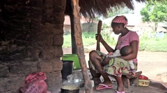 African woman smashing pepper with pistle, mortar, baby in lap Guinea Bisseau Stock Footage