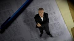 Tiny lawyer standing over contract paperwork Stock Footage