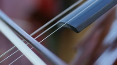 Playing the cello with a bow - stringed musical instrument closeup - stock footage