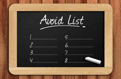 Stock Photo of Chalkboard on the wooden table written avoid list