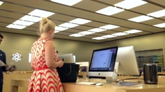 Motion of people buying new mac book Apple store - stock footage