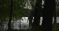 People at The RIver Bank, Trees' Trunks Silhouettes, Sun Hotspots Stock Footage