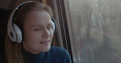 Woman traveling by train with favorite muisc Stock Footage