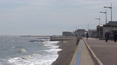 Long View of a Promenade as People Walk Up and Down Along the Beach Stock Footage