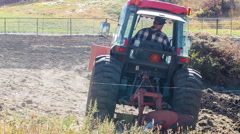 An Old Farmer Tills His Soil With A Large Tractor. Stock Footage
