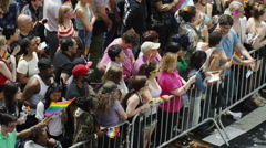 Crowded gay pride parade crowd behind barricade waving flags in NYC Stock Footage
