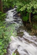 A beautiful cascading waterfall flows along a wooded Warren County Stock Photos