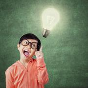 Funny little girl and bright light bulb - stock photo