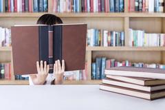 Stock Photo of Female kindergarten student reads literature