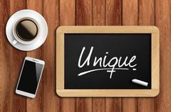 coffee, phone  and chalkboard with  word  unique - stock photo