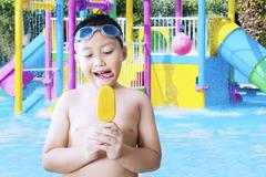 Small child eating ice cream at pool Stock Photos