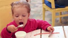 Baby girl dips a cookie in the milk shake Stock Footage